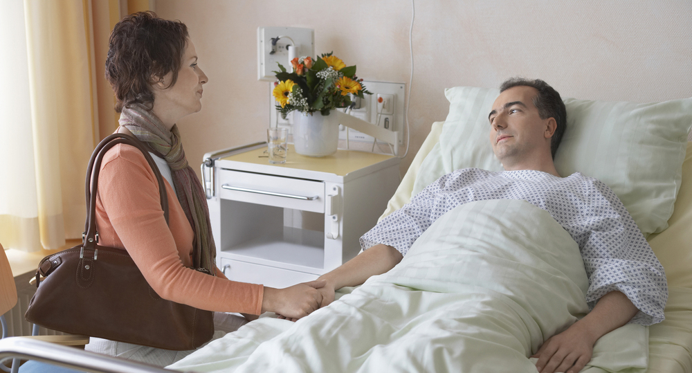 woman visiting patient in hospital bed - spinal cord injury