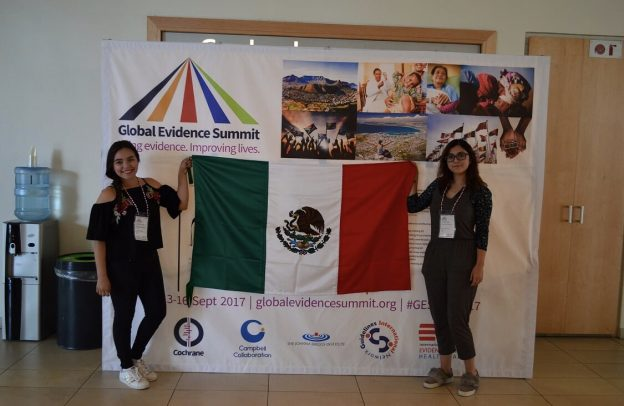 Cindy and Itzel standing next to the Global Evidence Summit poster
