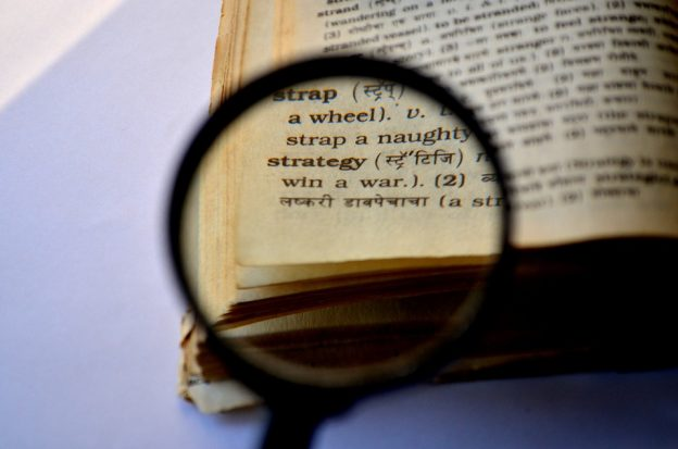 Strategy word shown behind a magnifying glass