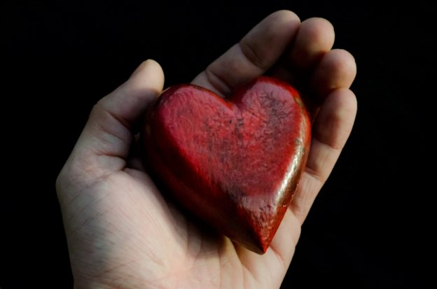 Hand holding red stone heart