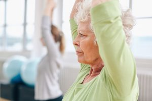 Older woman stretching up shoulder with younger woman next to her in class