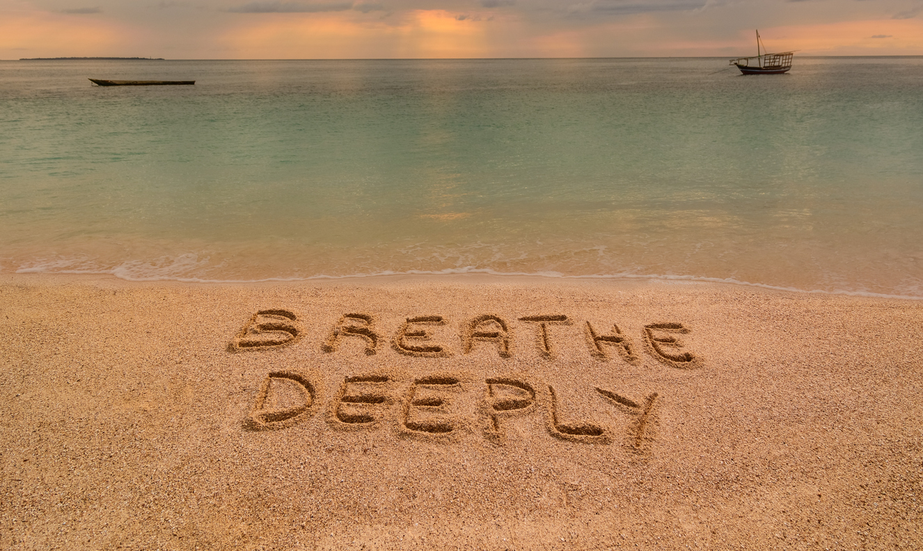 "In the photo a beach in Zanzibar at sunset where there is an inscription on the sand ""Breathe Deeeply""."