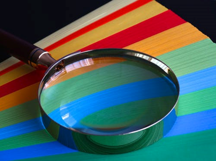 magnifying glass laid over coloured paper