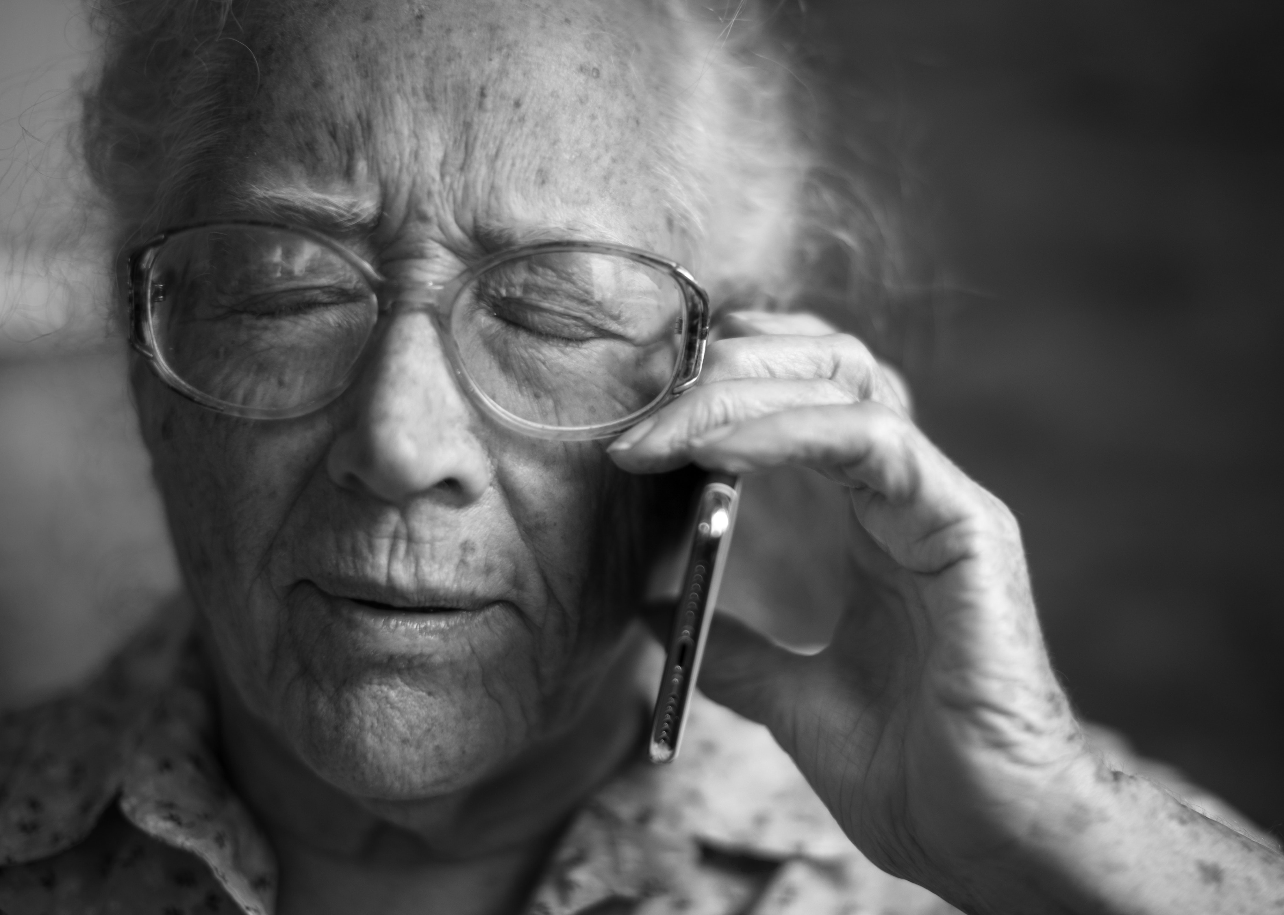 Older woman in black and white holding mobile phone